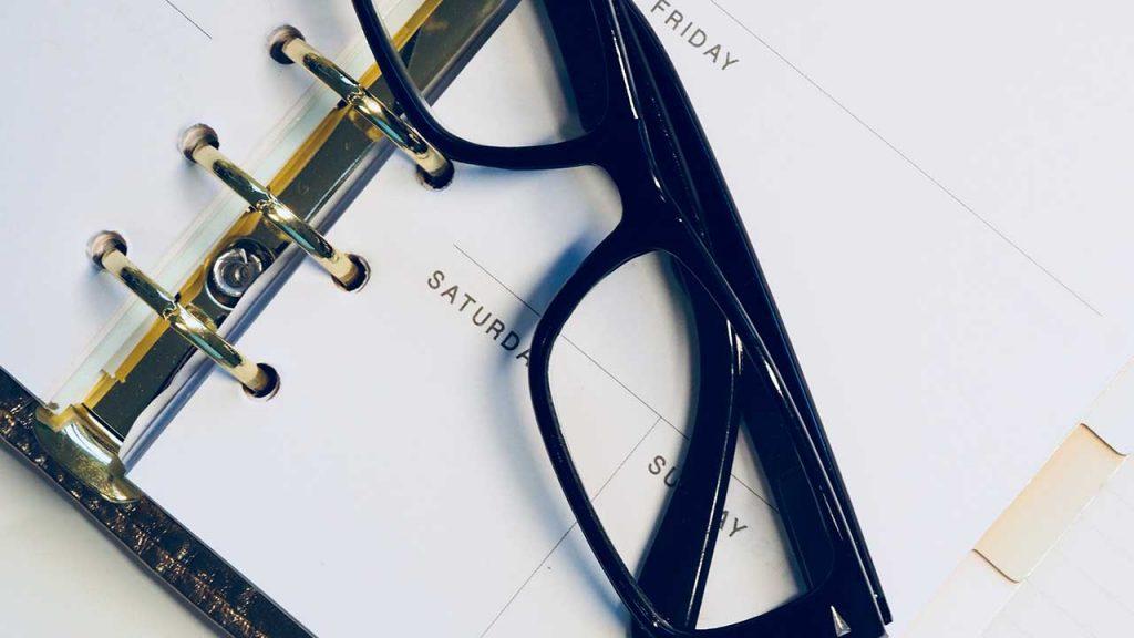 black-framed-wayfarer-style-eyeglasses-on-white-surface